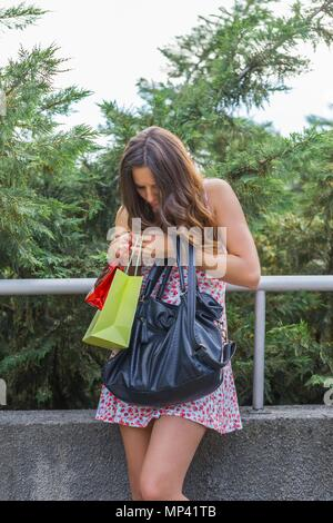 Teenager shopper outside in park with shopping bags in hands looking searching for something into bag - Stock Photo