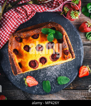 cheesecake with strawberries on a black graphite plate with a green sprig of mint, top view - Stock Photo