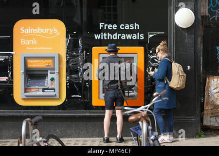A man withdrawing cash from a Sainsbury's ATM. - Stock Photo