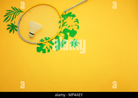 Summer vacation flat lay with badminton beach set and tropical leaves. Sports header on a bright yellow background with copy space. - Stock Photo