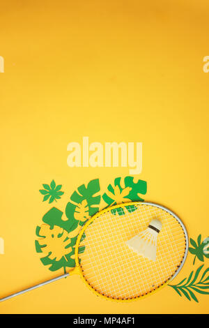 Badminton beach set. Summer activities flat lay with tropical leaves on a bright yellow background with copy space. - Stock Photo