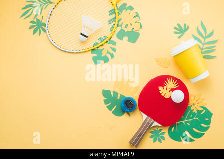 Badminton and ping pong beach set. Summer activities flat lay with tropical leaves on a bright yellow background with copy space. - Stock Photo