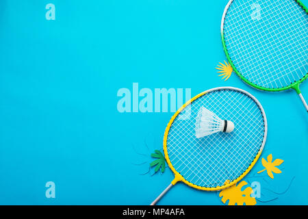 Badminton beach set and tropical leaves. Sports header on a bright blue background with copy space. Summer vacation flat lay - Stock Photo