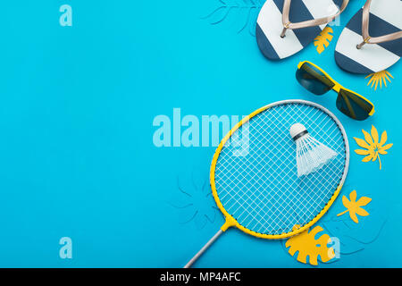 Badminton beach set, flip flops and tropical leaves. Sports header on a bright blue background with copy space. Summer vacation flat lay - Stock Photo