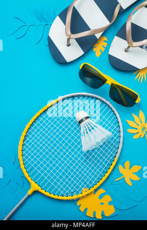 Badminton beach set, flip flopsm sunglasses and tropical leaves. Summer sports and recreation flat lay on a bright blue background with copy space. - Stock Photo