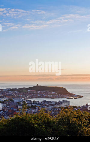 Scarborough's Castle headland and harbour at sunrise, seen from the summit of Oliver's Mount. - Stock Photo