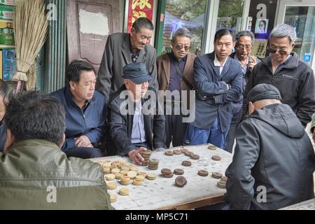 Old men playing Xiangqi, Chinese chess, Jiayuguan, Gansu, China - Stock Photo