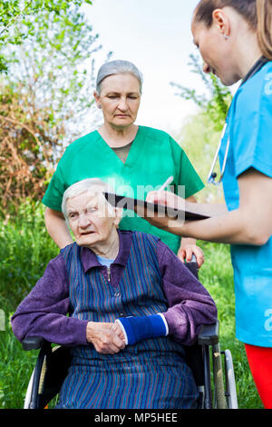Elderly sick woman in wheelchair, medical nurses discussing treatment outdoor - Stock Photo