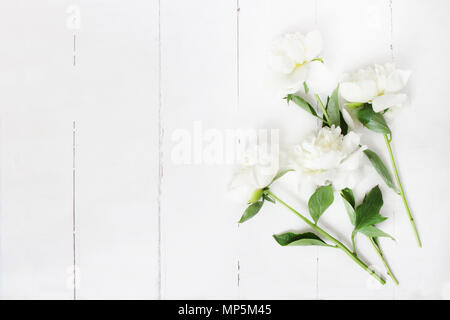 Styled stock photo. Feminine wedding table composition with white peonies flowers on old white wooden background. Empty space. Top view. Picture for blog. - Stock Photo