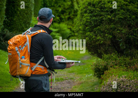 Hiker using map and compass for navigation - Stock Photo