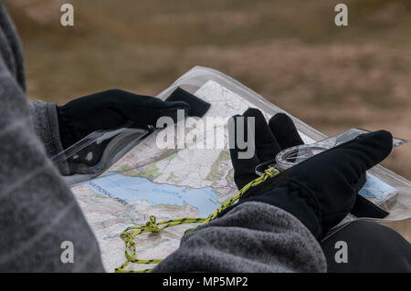 Walker using a compass and map to find way - Stock Photo