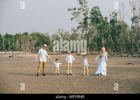 Portrait of an Asian Malaysian family looking very happy outdoors holding hand together. love and family concept - Stock Photo