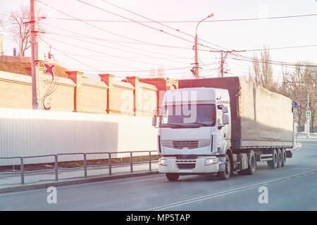 Big white truck passes through city street - Stock Photo