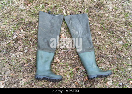 Boots for fishing on dry grass - Stock Photo