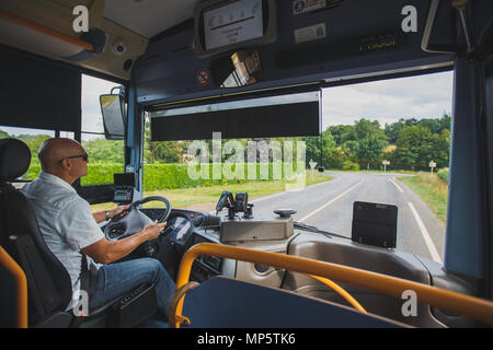 Theme is the profession of the driver and passenger transportation. A man in sunglasses A driver drives a tourist regional bus in the france region of - Stock Photo