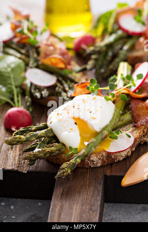 Asparagus and bacon bruschetta with poached egg - Stock Photo