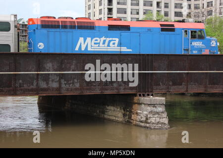 Metra train locomotive passing over a rusted bridge and stone abutment in the flooded des Plaines river. - Stock Photo