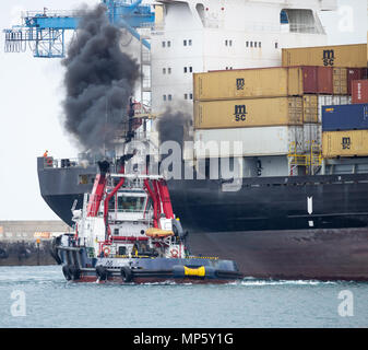 Tug boat belching out black smoke as it guides MSC Floriana container ship into port in Las Palmas on Gran Canaria Canary Islands, Spain - Stock Photo