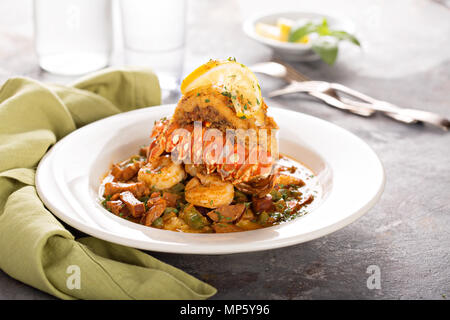 Grits with a lobster tail, shrimp and sausage - Stock Photo