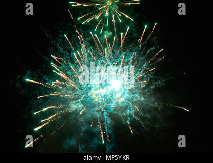 Colorful bright green fireworks and smoke in the night sky close-up background - Stock Photo