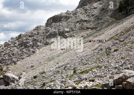 A hiking group crossing a rocky path footpath 526A beneath the cliffs of the Langkofel  Piz Sella above Selva Val Gardena Dolomites Italy - Stock Photo