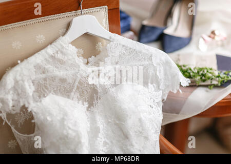 white wedding dress with lace lying on the chair. bouquet different flowers. Modern bridal bunch with poppy flower and thistle. bride accessories on the table - Stock Photo