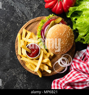 Tasty burger with beef, french fries and ketchup on dark background. Burger top view. Fast food fries and homemade cheeseburger. Square crop - Stock Photo