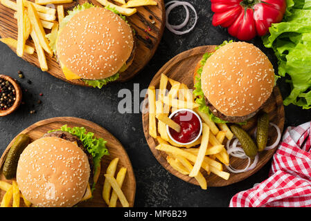 Tasty burgers, cheeseburgers, french fries, salad and red plaid kitchen textile, table top view. Three burgers or cheeseburgers, french fries and ketc - Stock Photo