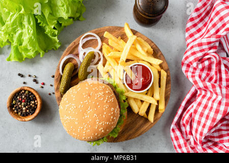 Burger with sesame, fries, pickles and lettuce salad. Top view of homemade beef burger with fries and pickles. Horizontal - Stock Photo