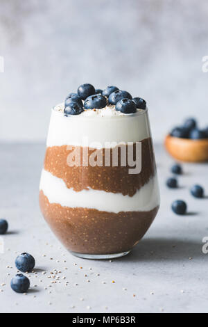 Layered chia pudding or healthy breakfast parfait with chocolate, yogurt, blueberries in a glass on concrete background. Copy space for text - Stock Photo