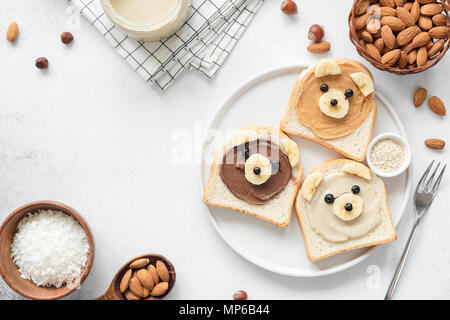 Animal face breakfast toasts with nut butter for kids on concrete background with copy space for text. Food art, kids menu or healthy vegan snack for  - Stock Photo