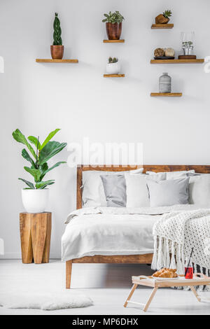 Breakfast tray standing on the floor beside a big comfortable bed with linen, blanket and pillows in a white bedroom interior. Real photo. - Stock Photo