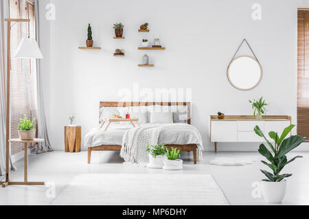 Morning in a bright and sunny modern white bedroom interior with wooden furniture. Cushions, blanket and food tray on the bed, nightstand beside and h - Stock Photo
