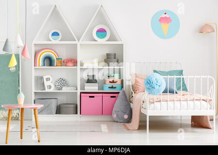 White kid's room interior with a single bed, rainbow on the shelf, pompom and ice-cream poster on the wall - Stock Photo