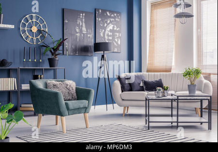 Navy blue living room interior with designer decor, black artwork and elegant comfortable sofa and armchair - Stock Photo