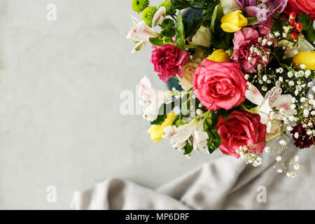 Top view of a colorful bouquet of beautiful flowers in the corner and gray blurry background with a piece of fabric