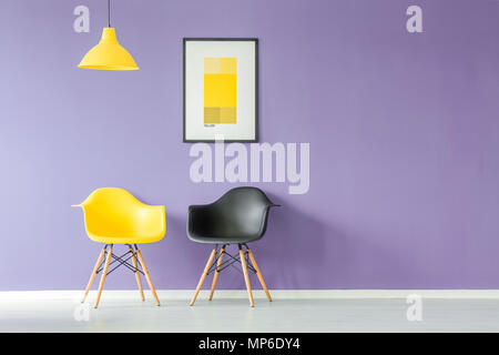 Front view of contrasting color, yellow and black chairs and a yellow lamp against purple background wall with a poster in a minimal living room inter - Stock Photo