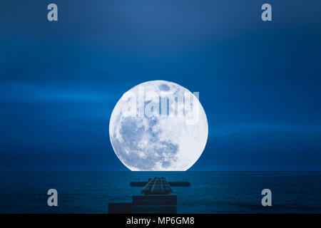 Old empty pier into the calm night sea with large full moon in the background - Stock Photo