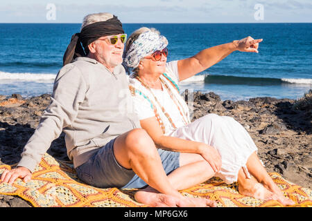 Couple of happy senior aged caucasian people sit down on the shore at the beach enjoying the summer time and the sun. Hippies alternative clothes for  - Stock Photo