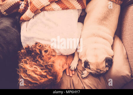 best friends forever with nice pug dog and beautiful swirl hair caucasian woman sleep together in the morning on the sofa. absolute friendship concept - Stock Photo