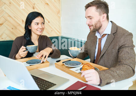 Business People Enjoying Conversation in Cafe - Stock Photo