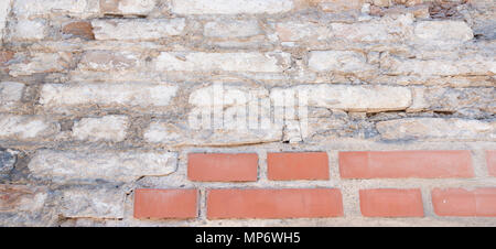 Old grungy red and white brick wall with damaged plaster banner background texture. - Stock Photo