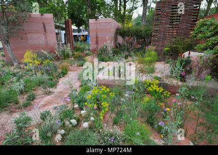 London, UK. 21st May 2018. The M&G Garden (designed by Sarah Price), one of the beautiful and elegant show gardens on display at the 2018 RHS Chelsea Flower Show which opened today in the 11-acre grounds of the Royal Hospital Chelsea, London, United Kingdom.  The garden is a romanticised haven set in a warm, sunny climate. It expands on a simple, timeless idea that three core elements - a wall, trees and seating - can create an intimate, sheltered and beautiful oasis of calm. Credit: Michael Preston/Alamy Live News