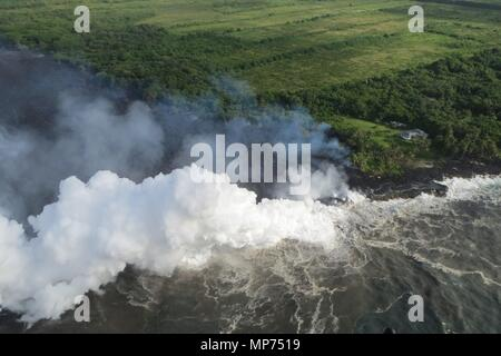 Hawaii, USA. 20th May 2018. Lava and poisonous sulfur dioxide plumes rise from fissure 20 as the molten magma reaches the ocean from the eruption of the Kilauea volcano May 20, 2018 in Pahoa, Hawaii. Hot lava entering the ocean creates a dense white plume called 'laze' (short for 'lava haze'). Laze is formed as hot lava boils seawater to dryness. Credit: Planetpix/Alamy Live News - Stock Photo