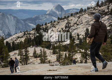 Yosemite, California, USA. 21st May, 2018. Yosemite National Park visitors walk on granite slabs above the Olmsted Point viewing area along Tioga Road (Highway 120 East). The road opened for the season to all vehicular traffic today, Monday, May 21, 2018.There are limited services available along Tioga Road, and all campgrounds along Tioga Road remain closed. Yosemite National Park is open year-round. For updated 24-hour road and weather conditions for Yosemite National Park, please call 209-372-0200. Credit: Tracy Barbutes/ZUMA Wire/Alamy Live News - Stock Photo