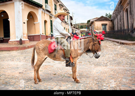 TRINIDAD CUBA, 14 JANUARY: Old men with cigar and donkey for rent in the street of colonial town Trinidad. Working in tourism is the only way cuban pe - Stock Photo