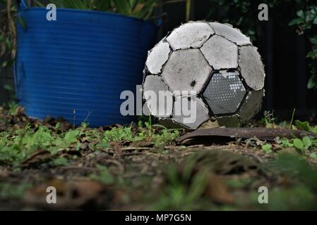 Torn up old soccer ball lay on grass. Worn out football. Concept of inactive person or useless object. - Stock Photo