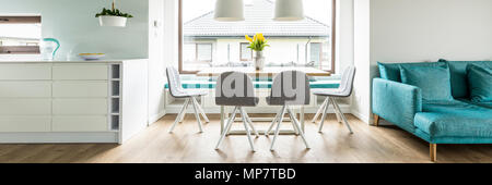 Panorama of grey chairs at table with yellow flowers next to blue settee in living room interior. Real photo - Stock Photo