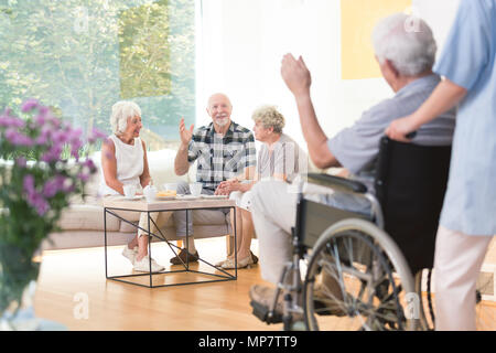 Group of senior people welcoming a friend while sitting together in living room - Stock Photo