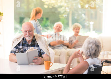Senior man reading a book and smiling while sitting with a friend at a table in nursing house - Stock Photo